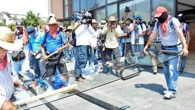 FOTO: Con sumo cuidado, manifestantes retiran una puerta de cristal del Congreso de Guerrero